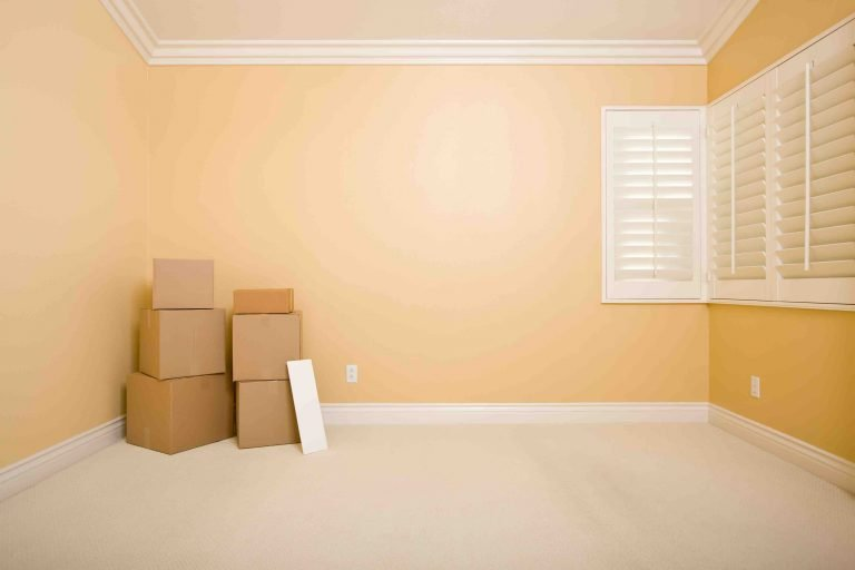 Moving Boxes and Blank Sign on Floor in Empty Room with Copy Space on Blank Wall.